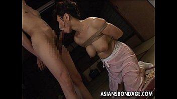 Bound Japanese MILF sucks on a hard cock