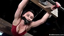 Brunette stretched in wooden stock device