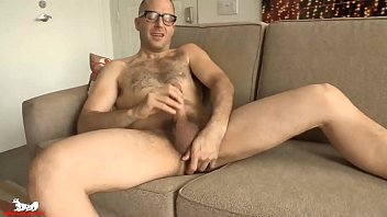 Joel starts jacking his cock as he bends over the sofa