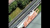 Mujer toma sol desnuda en balcon