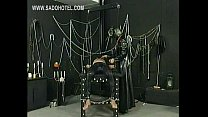 Masked dominatrix ties naughty slave to a workbench and put large clamps on his nipples