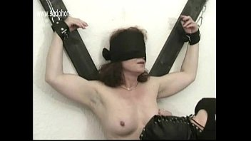 Milf slave tied to a wall gets her tight pussy finger fucked and spanked on her tits her master